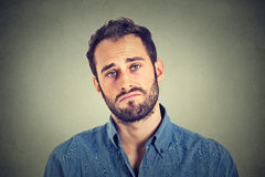 Sad young man  on gray wall background Royalty Free Stock Images