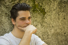 Sad young man with hand on chin thinking Royalty Free Stock Photography