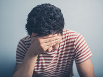 Sad young man with hand on forehead Royalty Free Stock Images