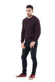 Sad young man with hands in pockets wearing sweater looking at camera. Full body length portrait isolated over white studio background Stock Image