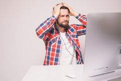 Sad young man with headset confused and unfappy look at monitor screen. Sad unhappy young man with head ache of losed games Royalty Free Stock Photo
