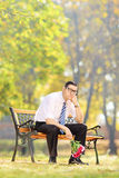 Sad young man holding a bouquet of flowers and sitting on bench Stock Images