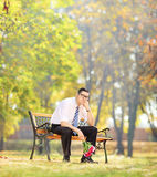Sad young man holding flowers and sitting on a bench in a park Royalty Free Stock Photos