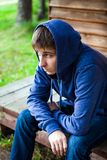 Sad Young Man outdoor. Sad Young Man in a Hoodie near the House outdoor Royalty Free Stock Images