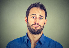 Sad young man isolated on gray wall background. Portrait of sad young man isolated on gray wall background Royalty Free Stock Photo