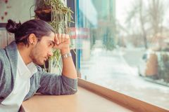 Sad young man looking down upset, hand on forehead royalty free stock images