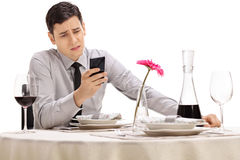 Sad young man looking at his cell phone Stock Photos