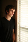 Sad young man looking out window Royalty Free Stock Image