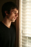 Sad young man looking out window Stock Photo