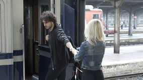 Sad young man in love caressing and saying goodbye to his girlfriend in railway station before departing on a rainy day stock footage