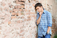 Sad young man near the brick wall Royalty Free Stock Photo