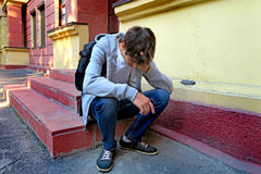Sad Young Man outdoor. Sad Young Man with Knapsack on the Porch of the House Stock Photography