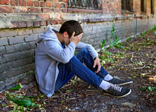 Sad Young Man outdoor. Sad Young Man near the Brick Wall of the Old House Royalty Free Stock Images