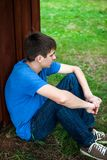 Sad Young Man outdoor. Sad Young Man sit on the Ground by the Wall Royalty Free Stock Images