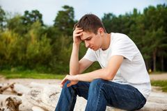 Sad Young Man outdoor. Sad Young Man sit on the Log on the Nature Background Royalty Free Stock Photos