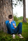 Sad Young Man outdoor. Sad Young Man sit under the Tree in the Park Royalty Free Stock Image