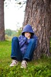 Sad Young Man outdoor. Sad Young Man sit under the Tree in the Park Royalty Free Stock Photo