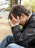 Sad Young Man outdoor. Sad Young Man sit in the Autumn Park Royalty Free Stock Photo