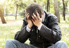Sad Young Man outdoor. Sad Young Man sit in the Autumn Park Royalty Free Stock Image