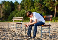 Sad Young Man outdoor. Sad Young Man sit on the Bench outdoor Stock Image