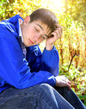 Sad Young Man outdoor. Sad Young Man in the sit in the Forest Stock Photo