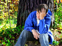 Sad Young Man outdoor. Sad Young Man in the sit in the Forest Stock Image