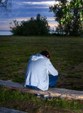 Sad Young Man outdoor. Sad Young Man sit on the Log outdoor Royalty Free Stock Images