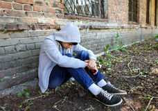Sad Young Man outdoor. Sad Young Man sit near the Brick Wall of the Old House Royalty Free Stock Image