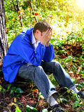 Sad Young Man outdoor. Sad Young Man sit under the Tree in the Forest Stock Photography