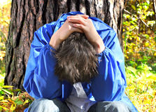 Sad Young Man outdoor. Sad Young Man sit under the Tree in the Forest Royalty Free Stock Photos