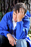 Sad Young Man outdoor. Sad Young Man sit under the Tree in the Forest Royalty Free Stock Image