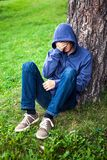 Sad Young Man outdoor. Sad Young Man sit under the Tree in the Park Stock Photos