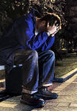 Sad Young Man outdoor. Sorrowful Young Man sit on the Bench in the Night Park Royalty Free Stock Image