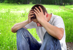 Sad Young Man outdoor. Sorrowful Young Man sit on the Nature Background Royalty Free Stock Photos