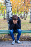 Sad Young Man outdoor. Stressed Young Man sit on the Bench in the Autumn Park Stock Photos