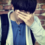 Sad Young Man outdoor. Toned Photo of Sad Young Man on the Brick Wall Background Royalty Free Stock Photography