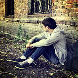 Sad Young Man outdoor. Toned Photo of Sad Young Man near the Brick Wall of the Old House Stock Photography