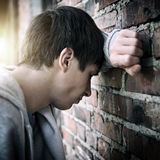 Sad Young Man outdoor. Toned Photo of Sad Young Man by the Old Brick Wall Royalty Free Stock Photography