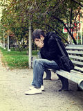 Sad Young Man outdoor. Toned Photo of Sad Young Man sit on the Bench at the City Street Stock Images