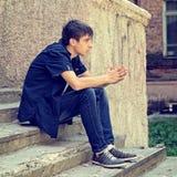 Sad Young Man outdoor. Toned Photo of Sad Young Man sit on the City Street Stock Photos
