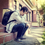 Sad Young Man outdoor. Toned Photo of Sad Young Man sit on the Porch of the House Royalty Free Stock Photo