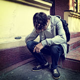 Sad Young Man outdoor. Toned Photo of Sad Young Man sit on the Porch of the House Royalty Free Stock Images