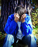 Sad Young Man outdoor. Toned Photo of Sad Young Man sit under the Tree in the Forest Royalty Free Stock Photos