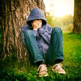 Sad Young Man outdoor. Toned Photo of Sad Young Man sit under the Tree in the Park Stock Photos