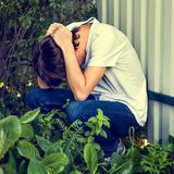 Sad Young Man outdoor. Toned Photo of Sad Young Man sit by the Wall outdoor Stock Image