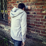 Sad Young Man outdoor. Toned Photo of Sad Young Man by the Wall outdoor Stock Photo