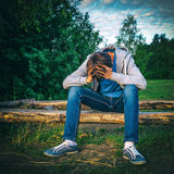 Sad Young Man outdoor. Vignetting Photo of Sad Teenager sit on the Log outdoor Royalty Free Stock Images