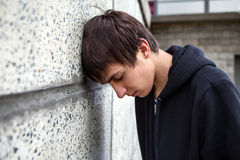Sad Young Man outdoor. Sad Young Man by the Wall outdoor Royalty Free Stock Photography