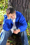 Sad young man with phone Stock Images