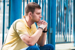 Sad young man portrait in the open air. Sad young man portrait on a background of blue fence Stock Photos